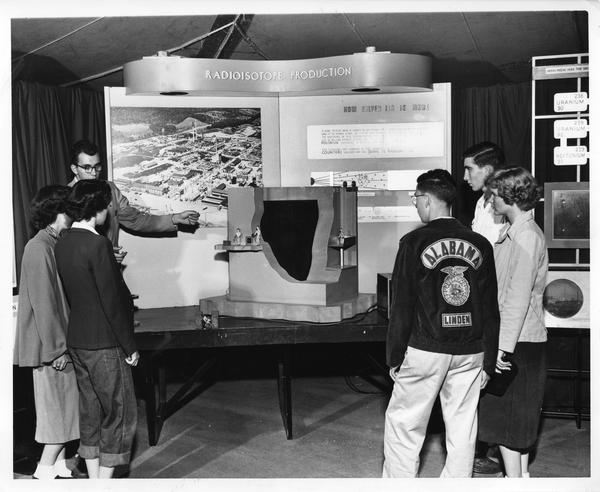 Students gathered in front of a model atomic pile at the Atomic Energy Exhibit