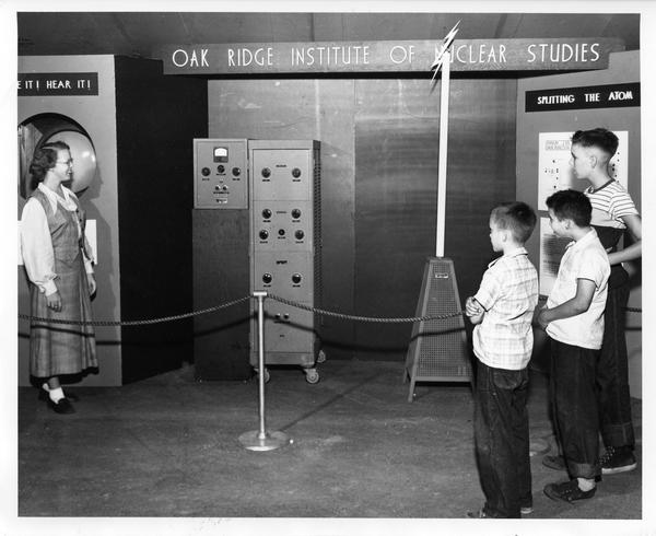 Students look on as an exhibit demonstrator explains equipment at the traveling Atomic Energy Exhibit