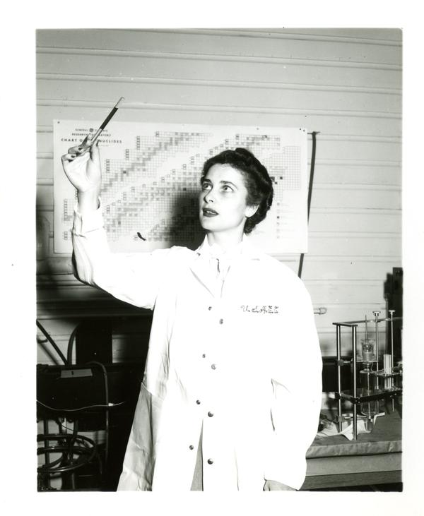 """Frances Miller of the Atomic Energy Project holds up a """"dosimeter,"""" an atomic radiation indicator"""