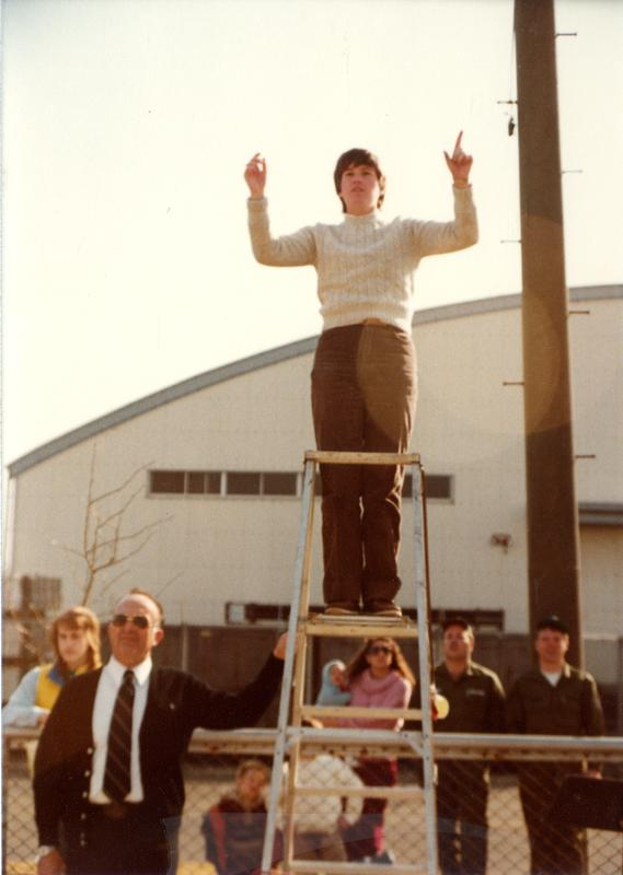 Band director leading on ladder as spectators look on from the sidelines