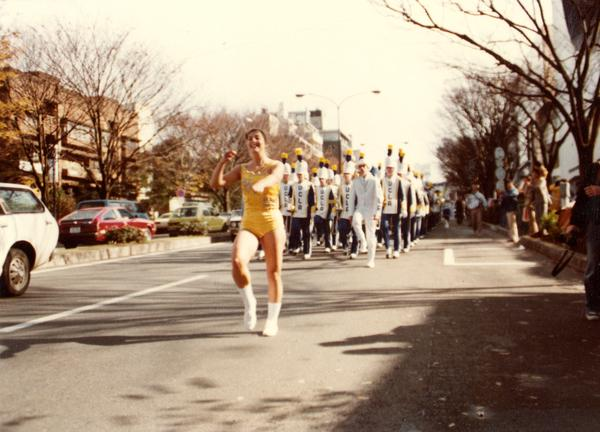 Dancer leading marching band on street