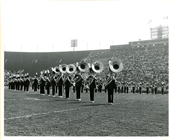 Marching band brass players performing in football stadium