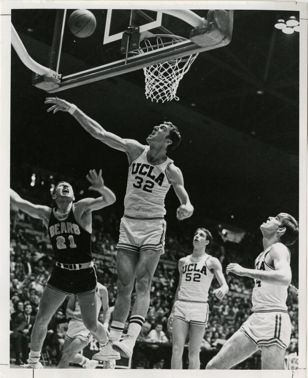 Both Steve Patterson (32) and a member of the Cal Bears give the basketball a disapproving look.