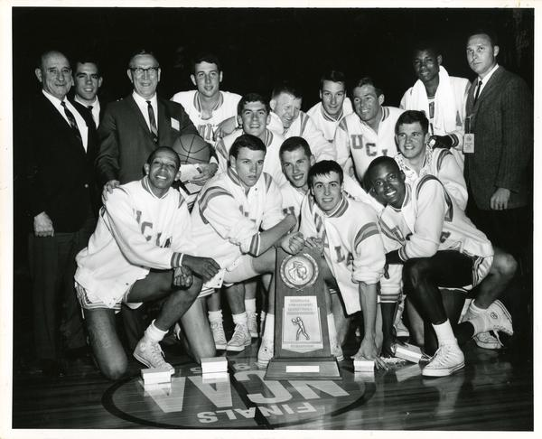 Team portrait on court with NCAA trophy, 1965