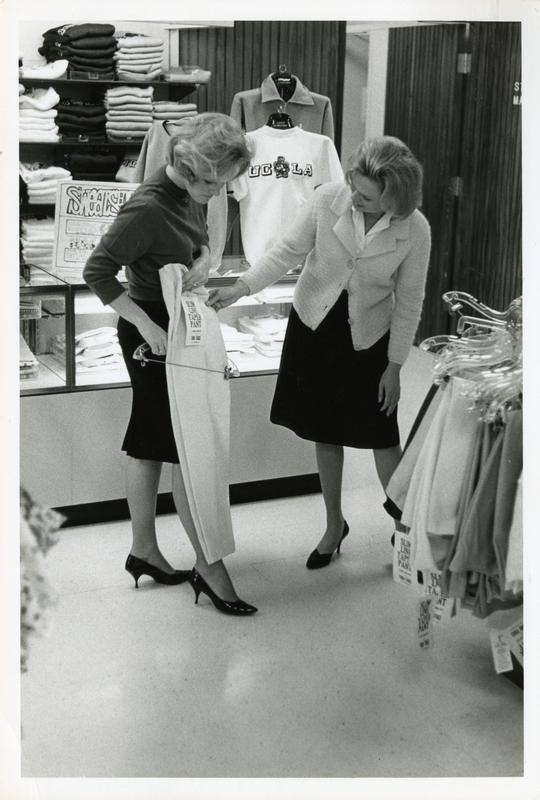 Two women examining a pair of pants in the student store