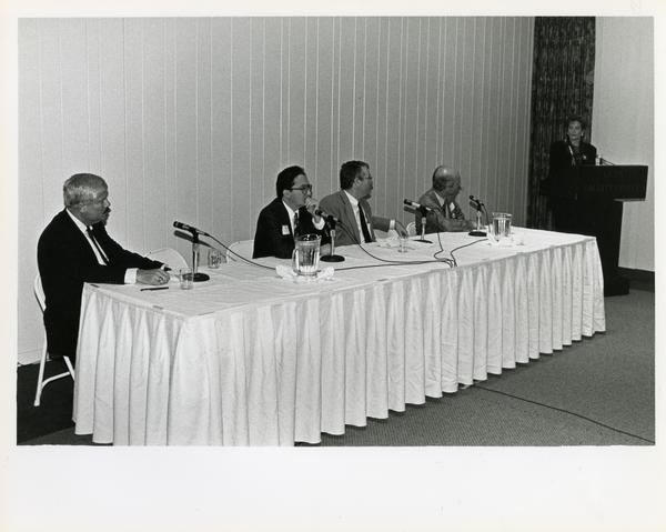 Panel of speakers seated at table, Breslow Lecture, 1991