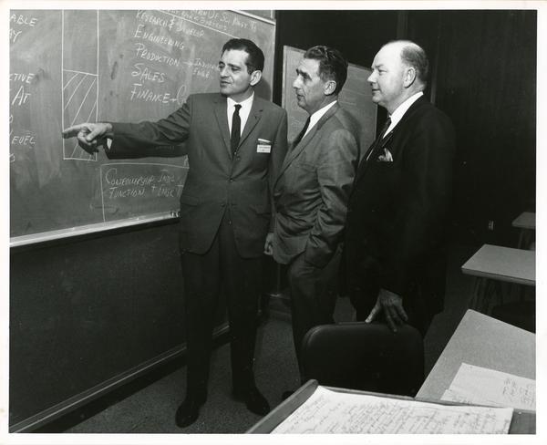 Participants conversing at chalkboard at California Newspaper Publishers Seminar, January 1966