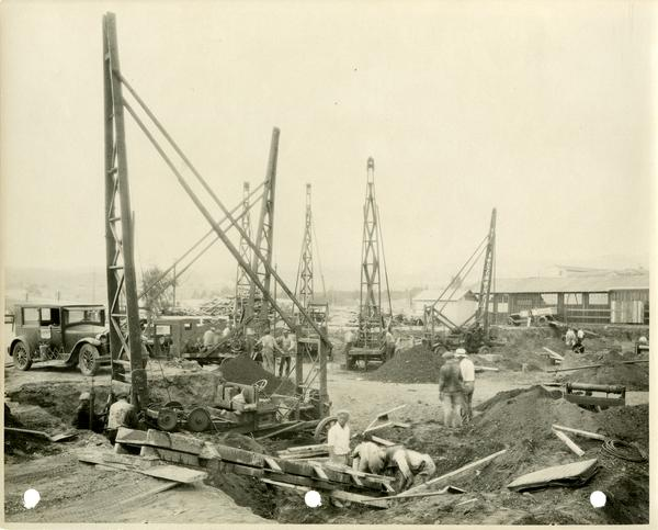 Construction zone with tall equipment and workers