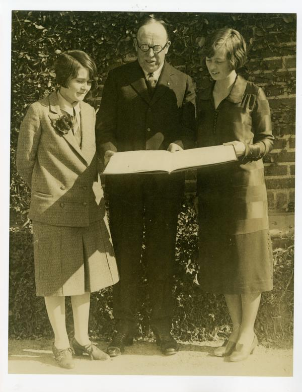 One man and two women looking at large book