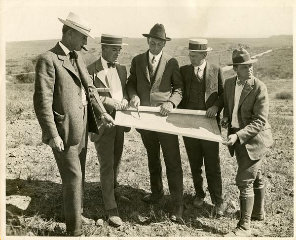 Herbert Foster, Robert Underhill, Stagg Gregg, and two other men looking at a map