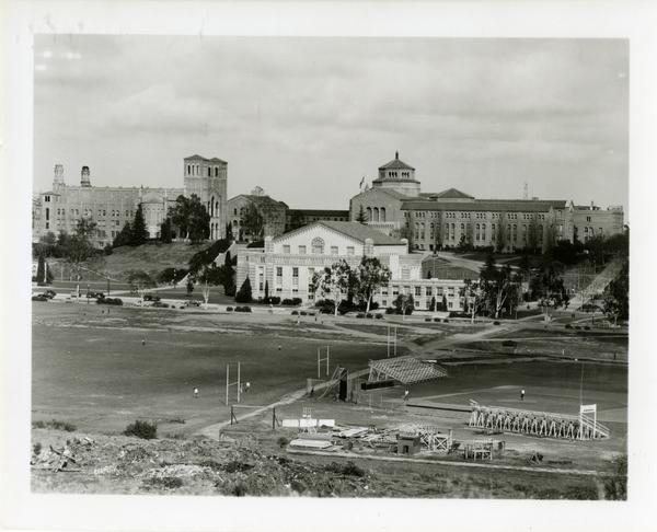 Students on the athletic field with Student Activities Center, Royce Hall and Powell Library in the background