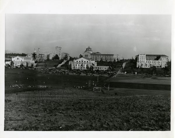 Students on the athletic field with Student Activities Center, Royce Hall and Powell Library in the background, ca. 1938