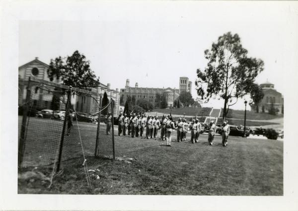 Drill team practicing on soccer field with Janss Steps leading up to Kaufman Hall, Royce Hall and Powell Library in the background, June 1943