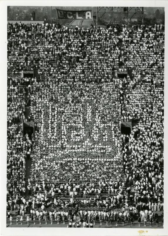 Students holding up cards spelling out UCLA at the football game, ca. 1955