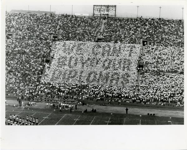 "Crowd holds cards that say ""We Can't Buy Our Diplomas"" at the football game, ca. 1950"