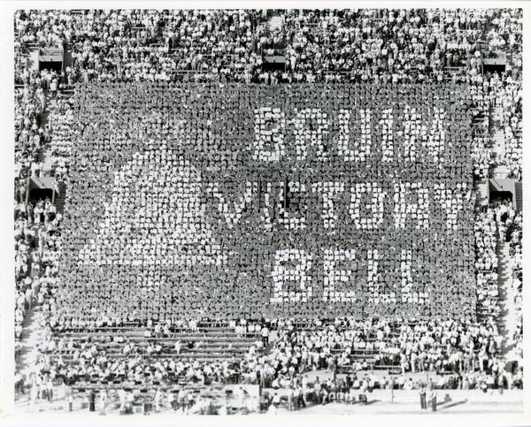 "Crowd holds up cards that spell out ""Bruin Victory Bell"" and form a bell at football game, 1955"