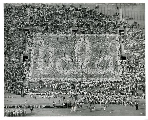 Crowd holds up cards that say UCLA at the football game, 1965