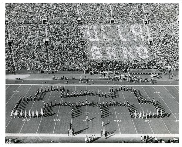 "Marching band forms the shape of Royce Hall on footbal field with crowd holding up signs that spell ""UCLA BAND"" in the background, 1971"