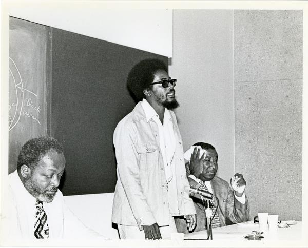 Man standing up among a panel of speakers at the Center for African American Studies