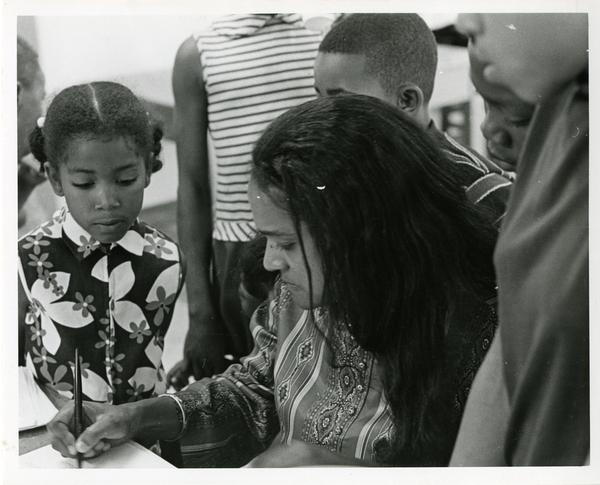 Woman writes as children look on