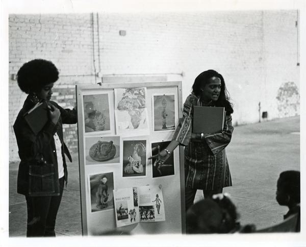 Two unidentified women presenting artwork to children at Center for African American Studies