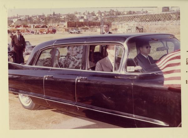 President Johnson in a limousine with guards around the vehicle, charter day 1964