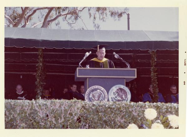 UCLA Chancellor Murphy speaks at podium on Charter Day 1964