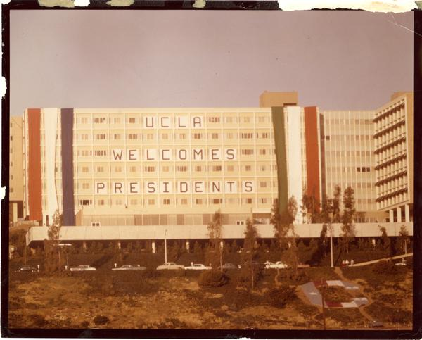 "Residence Hall building displaying sign ""UCLA Welcomes Presidents,"" Charter Day 1964"