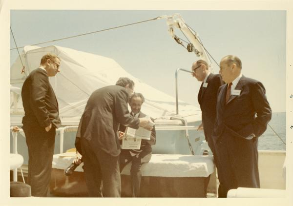 Emperor Haile Selassie of Ethiopia looking over documents on Motor Yacht Argo, 1967