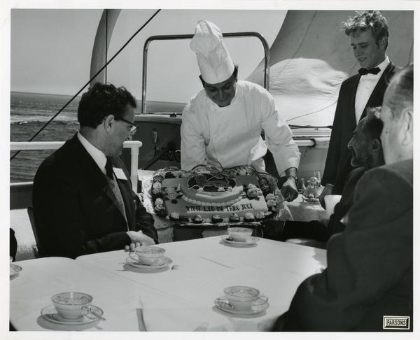 Chef presenting cake to Emperor Haile Selassie of Ethiopia upon Motor Yacht Argo, April 25, 1967