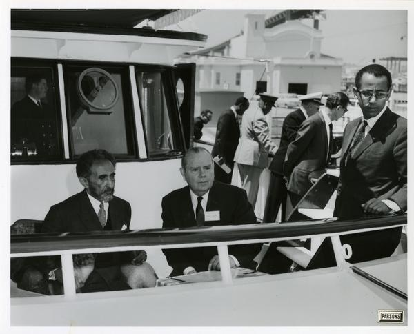 Emperor Haile Selassie with his dog and men sits at rail of Motor Yacht Argo, April 25, 1967