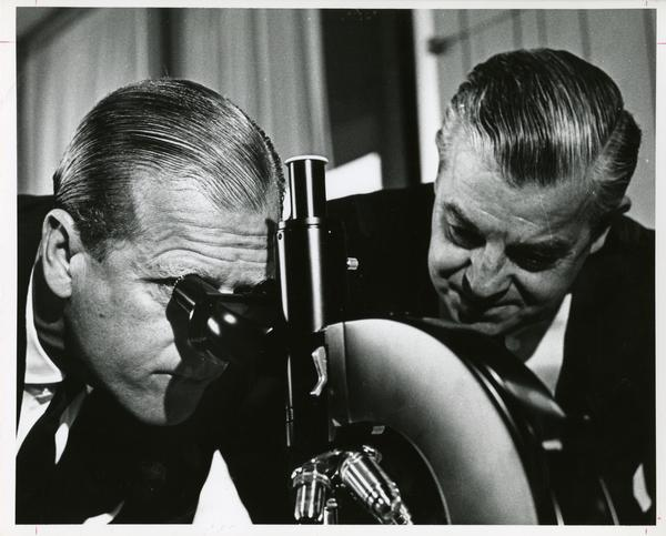 Prince Philip looks into a microscope with a UCLA professor