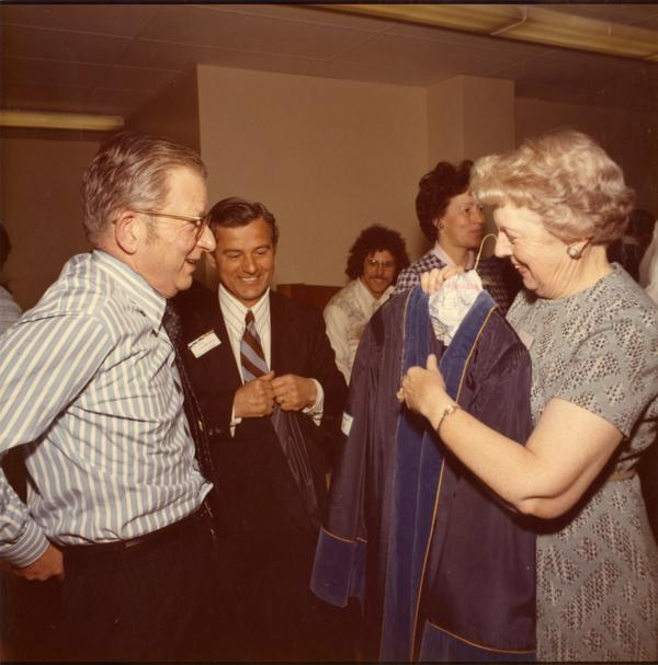 President Hitch being assisted with his robes by Patty Carver and Paul Christopolos, Charter Day 1975