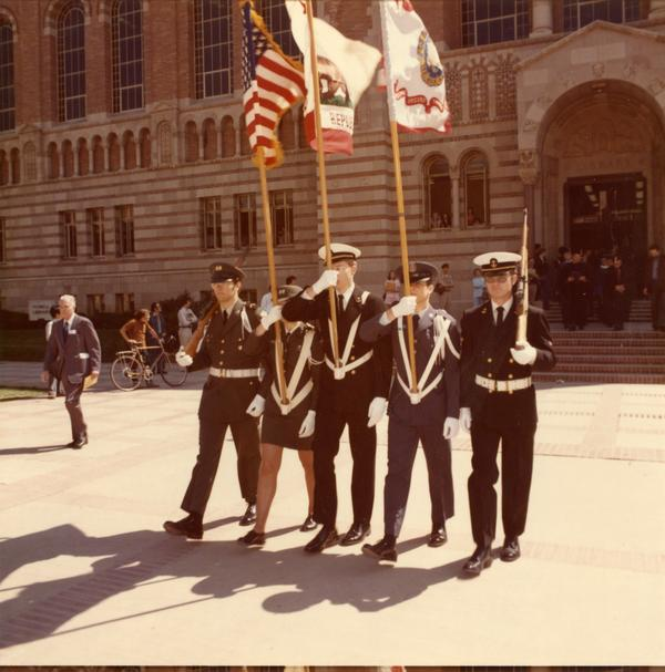 Color guard marching in front of Powell Library on Charter Day