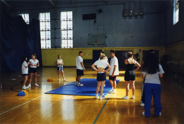 Cheerleaders gathered around in the gym