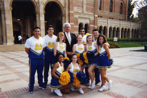 UCLA cheerleaders pose with unidentified man in front of Royce Hall
