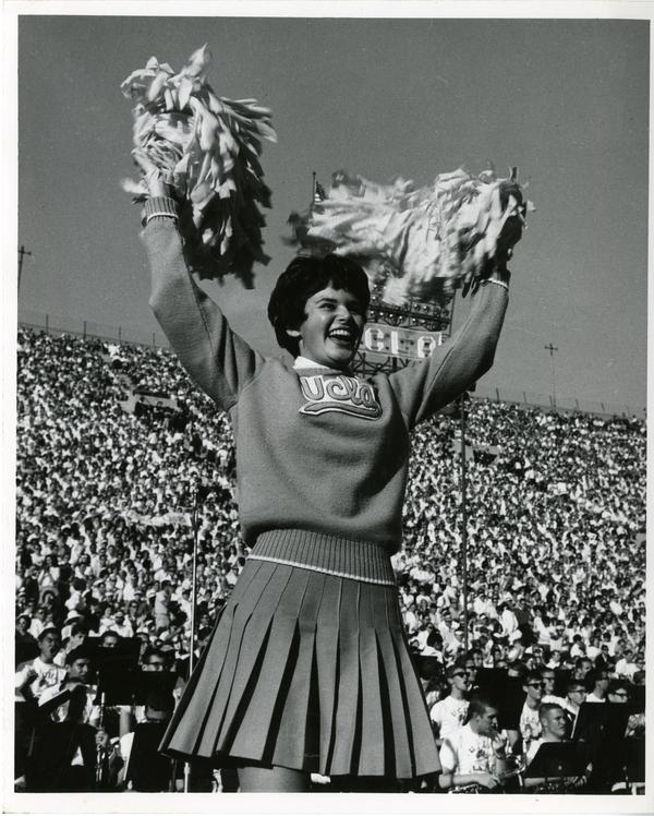UCLA cheerleader performing at a football game, ca. 1960's