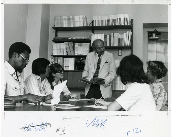 Instructor speaking with small group of students, circa 1980's