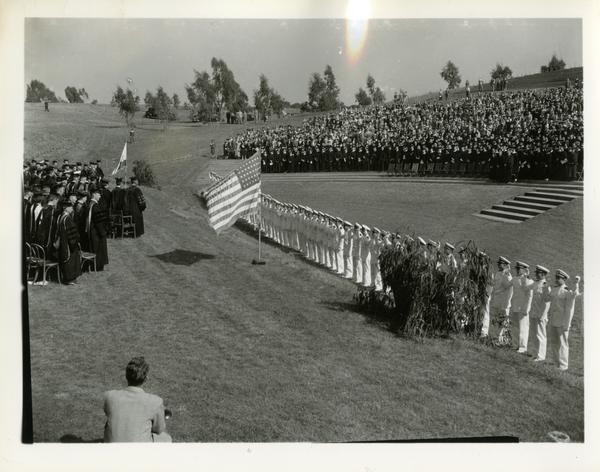 View of crowd during flag salute at Commencement, circa 1940's