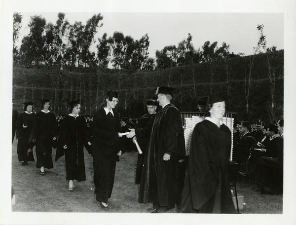 Graduates receiving their diplomas at Commencement, circa 1940's