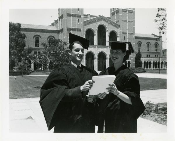Two graduates pose after Commencement, circa 1950's