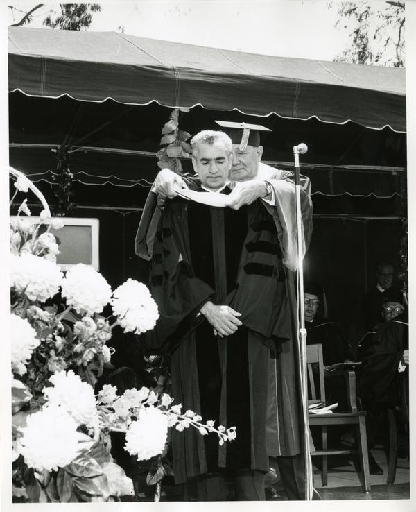 Regent Edwin Pauley hooding Mohammad Reza Pahlavi, the Shah of Iran, at Commencement, 1964