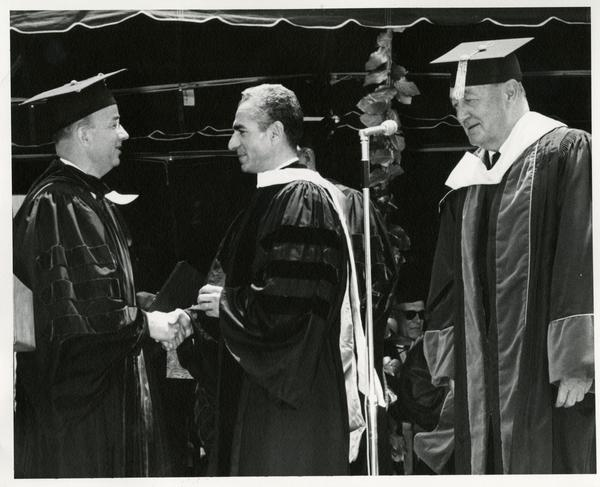 President Clark Kerr shaking hands with Mohammad Reza Pahlavi, the Shah of Iran, while Regent Edwin Pauley looks on at Commencement, 1964