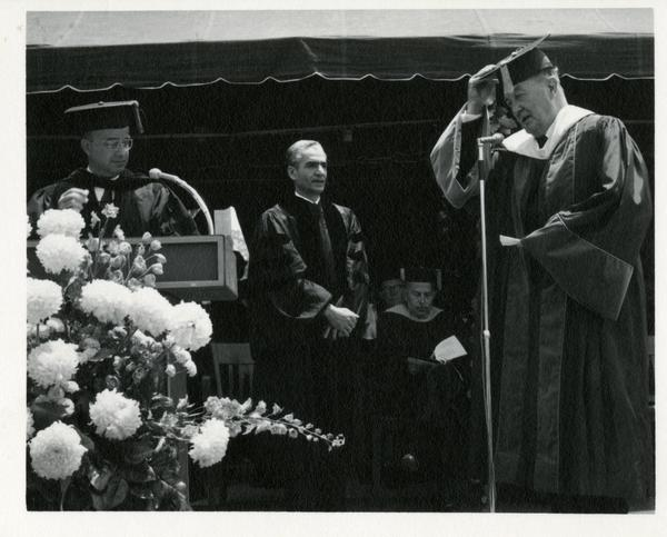 Mohammad Reza Pahlavi, the Shah of Iran, receiving his honorary degree from President Clark Kern and Regent Edwin Pauley at Commencement, 1964