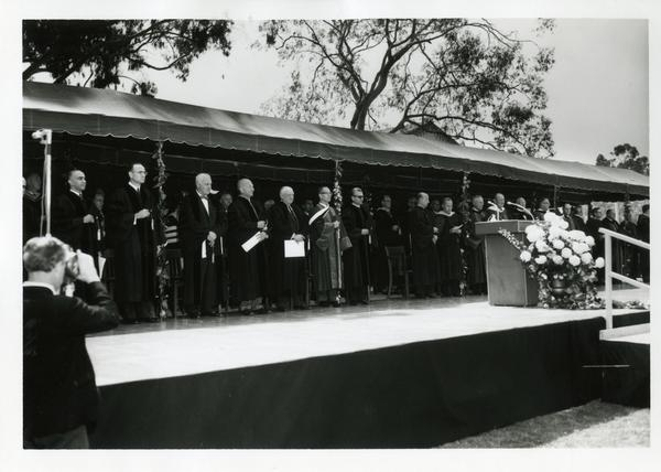 Faculty and speakers standing up on stage at Commencement, 1964