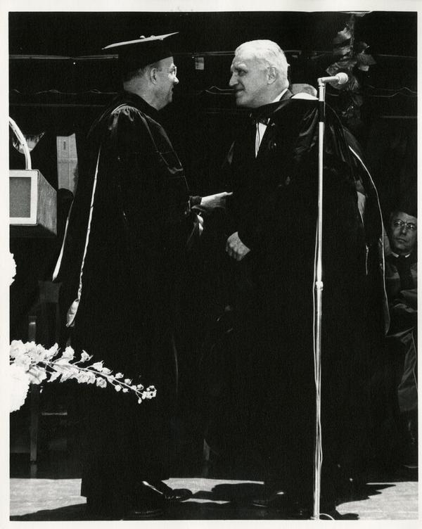 President Clark Kerr shaking hands with a unidentified man at Commencement, 1964