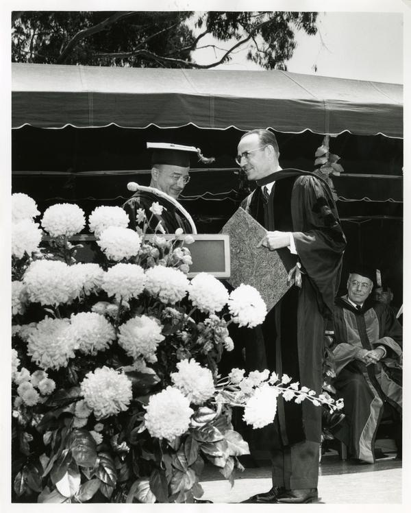 President Clark Kerr shaking hands with a unidentified man on stage at Commencement, 1964