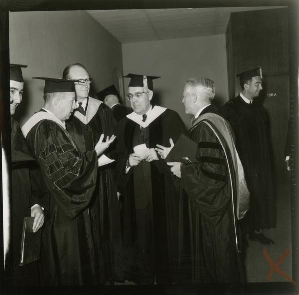 Contact print of faculty and staff gathered around after Mid-Year Commencement, January 28, 1964