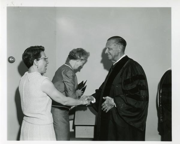 Unidentified women and man at Commencement, June 9, 1966
