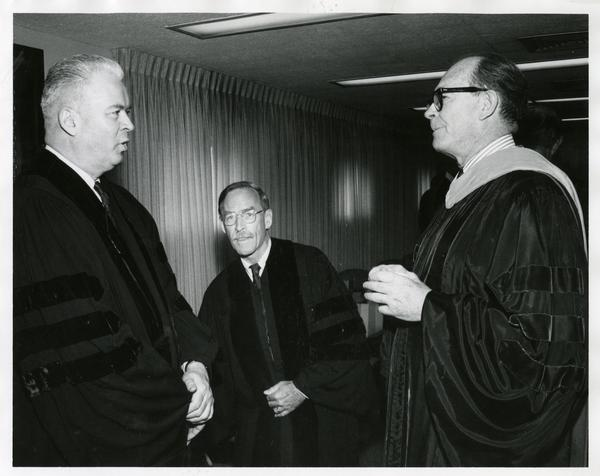 Faculty and administration talking at Commencement, 1968